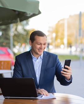 Ein überraschter geschäftsmann sitzt an einem tisch in einem café auf der straße und arbeitet an seinem handy in einem geschäftsviertel der stadt. daneben steht ein laptop.