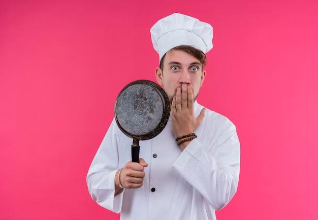 Ein überraschter junger bärtiger kochmann in der weißen uniform, die bratpfanne mit hand auf mund hält, während er auf eine rosa wand schaut