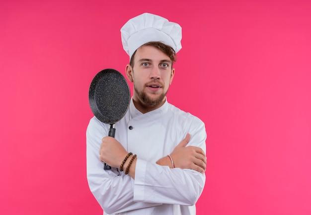 Ein überraschter junger bärtiger kochmann in der weißen uniform, die kochmütze hält, die pfanne hält, während auf einer rosa wand schaut