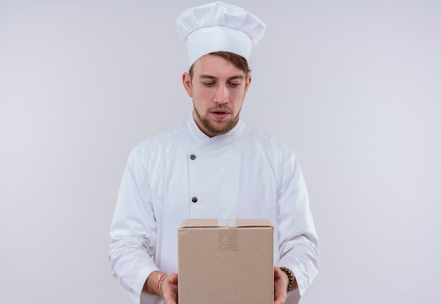 Ein überraschter junger bärtiger kochmann in der weißen uniform, die lieferbox hält und es auf einer weißen wand betrachtet
