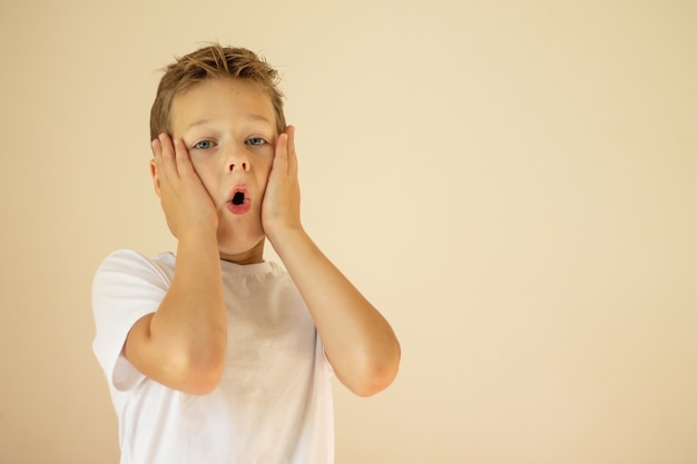 Ein überraschter oder verängstigter junge von 7-10 jahren in einem weißen t-shirt steht und schreit mit den händen auf den wangen auf beigefarbenem hintergrund. platz kopieren.