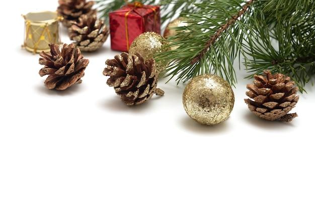 Ein üppiger tannenzweig, mit goldglitter verzierte tannenzapfen, glänzende goldkugeln, eine spielzeugtrommel, ein geschenk in einer roten hülle auf weißem hintergrund. vorlage für grußkarte oder einladung.