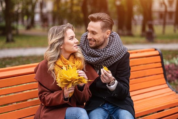 Ein umarmender mann fand ein kleines blattglückliches paar, das auf der bank saß und im park umarmt war und mäntel und schals trug, die einen strauß gefallener blätter sammelten