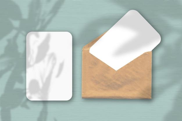 Ein umschlag mit zwei blättern strukturiertem weißem papier auf einem grauen tischhintergrund. modell mit einer überlagerung von pflanzenschatten. natürliches licht wirft schatten vom baum des glücks.
