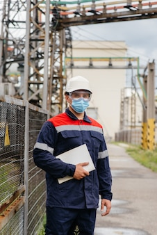 Ein umspannwerkingenieur inspiziert moderne hochspannungsgeräte in einer maske zum zeitpunkt der pandämie. energie. industrie.