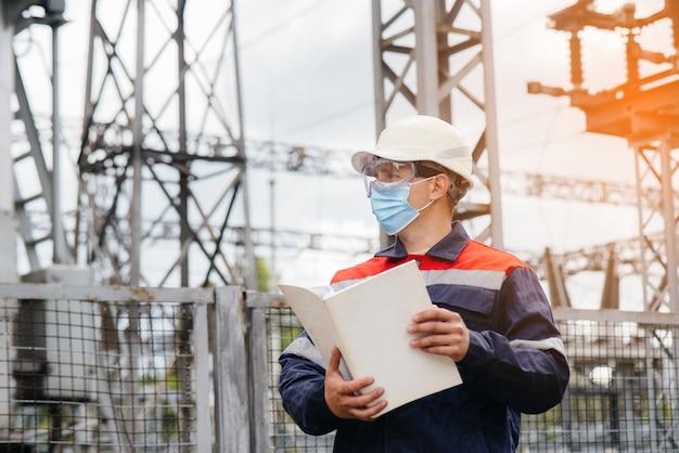 Ein umspannwerkingenieur inspiziert moderne hochspannungsgeräte in einer maske zum zeitpunkt der pondämie. energie. industrie.