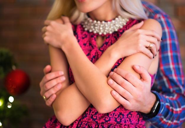 Ein unbekannter mann umarmt seine schöne junge frau