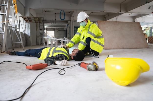 Ein unfall eines arbeiters auf der baustelle. die helfen den verletzten in der vorwahl. auswahlfokus auf eine verletzte person.