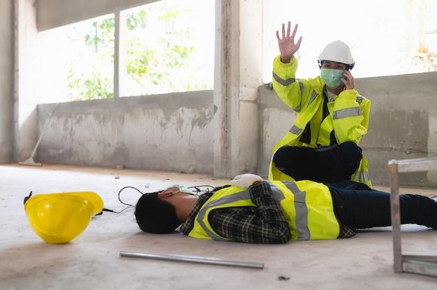 Ein unfall eines arbeiters auf der baustelle und anruf beim sicherheitsbeauftragten für rettung und lebensrettung. auswahlfokus auf eine verletzte person.