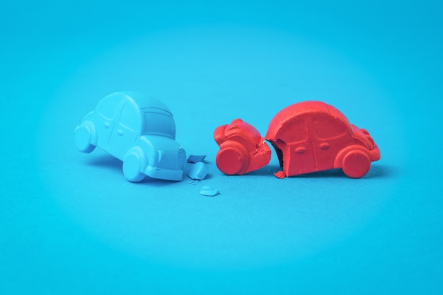 Ein unfall zwischen einem roten und einem blauen auto auf einem blauen hintergrund. ein verkehrsunfall.