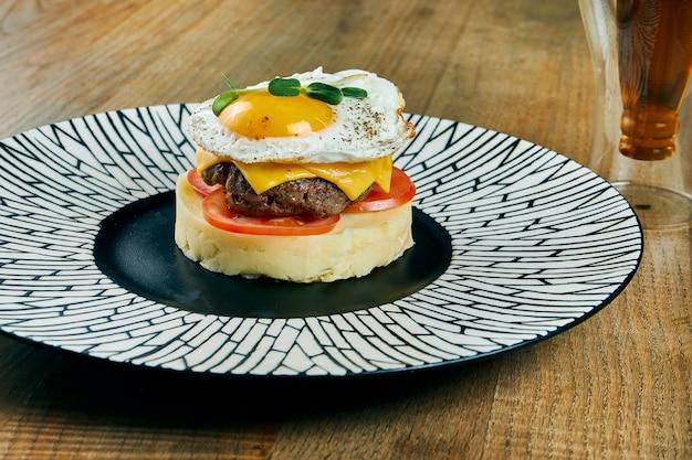 Ein ungewöhnliches gericht - ein burger aus kartoffelpüree, tomaten, rindfleischpastetchen, cheddar-käse und spiegeleiern auf einem keramikteller. nahaufnahme des essens