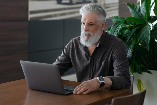 Ein unglaublich schöner und stilvoller grauhaariger mann von fünfzig jahren, der mit einem laptop arbeitet