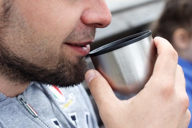 Ein unrasierter mann trinkt kaffee oder tee aus einer thermoskanne, ganz nah.