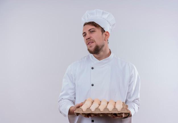 Ein unzufriedener junger bärtiger männlicher kocher, der weiße kochuniform und einen hut hält, der einen karton eier hält, während er auf eine weiße wand schaut