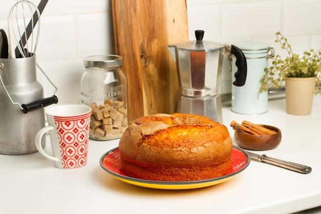Ein vanillekuchen auf einem roten teller auf der küchenarbeitsplatte