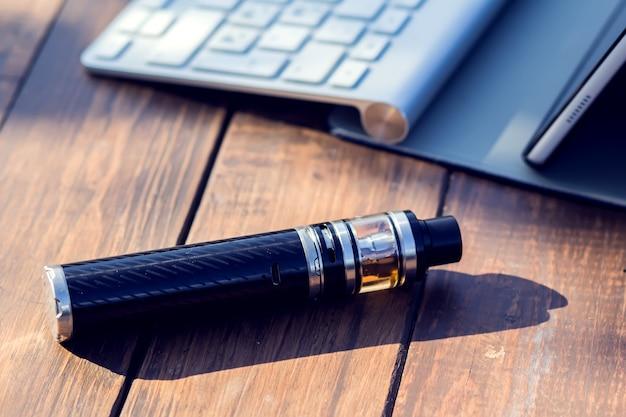 Ein vaporizer und ein laptop stehen auf dem holztisch. raucherstellung. lifestyle-konzept