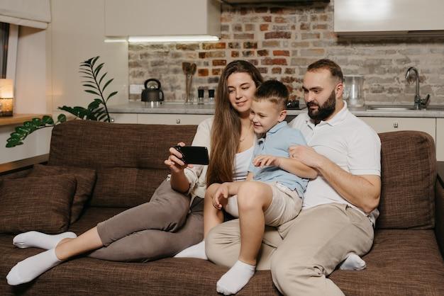 Ein vater, ein sohn und eine junge mutter schauen sich ein video auf einem smartphone auf dem sofa an
