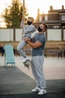 Ein vater hilft seinem sohn, während des sonnenuntergangs in masken in masken auf ein seil auf einem sportplatz zu klettern. gesunde elternschaft und gesunder lebensstil.