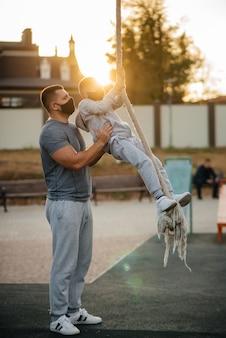 Ein vater hilft seinem sohn, während des sonnenuntergangs mit masken auf einem sportplatz ein seil zu klettern
