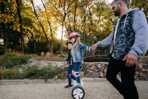 Ein vater hilft und bringt seinen kleinen kindern bei, bei sonnenuntergang einen segway im park zu fahren