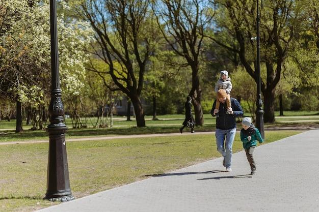 Ein vater rennt mit seinen beiden söhnen die gasse entlang. im herbst zeit mit kindern an der frischen luft verbringen. sankt petersburg, russland