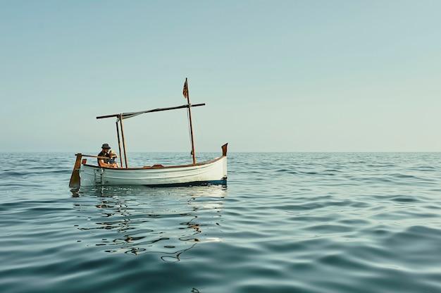 Ein vater und ein sohn, die in einem klassischen weinleseboot segeln