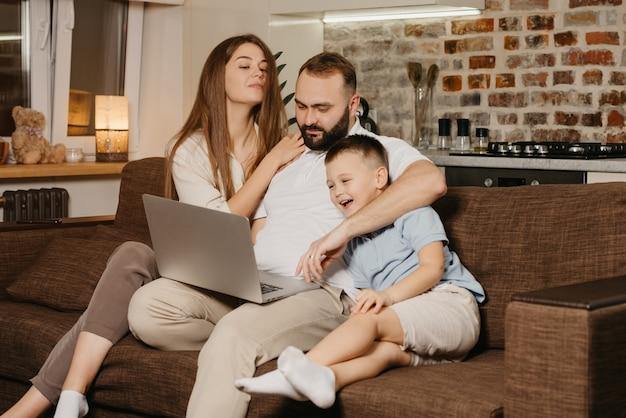Ein vater versucht, in der nähe seines lächelnden sohnes und einer neugierigen frau zu hause an einem laptop zu arbeiten