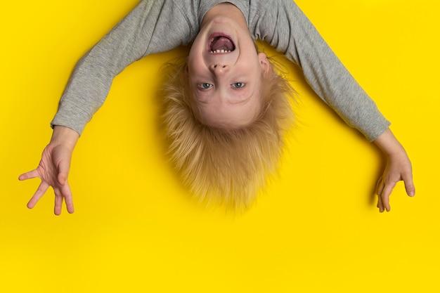 Ein verängstigter junge mit blonden langen haaren hängt kopfüber und schreit.