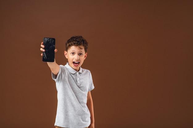 Ein verängstigter kleiner junge hat sein smartphone durcheinander gebracht