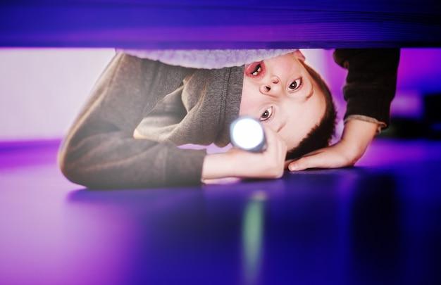 Ein verängstigter kleiner junge schaut mit einer taschenlampe unter das bett. angst vor der dunkelheit, ängste der kinder.
