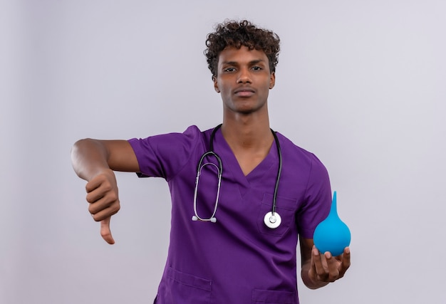Ein verärgerter junger gutaussehender dunkelhäutiger arzt mit lockigem haar in violetter uniform mit stethoskop, das die daumen nach unten zeigt, während er einen einlauf hält