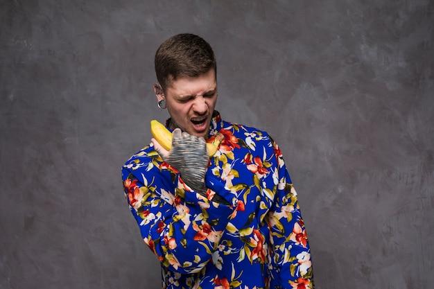 Ein verärgerter junger mann mit tätowiert auf seiner hand schreit am bananentelefon gegen graue wand