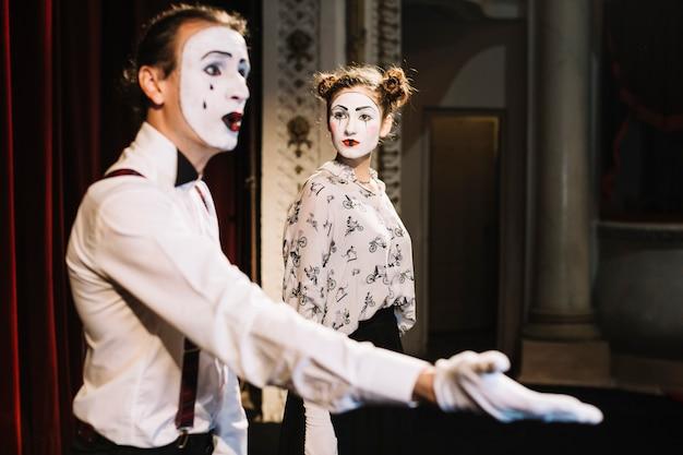 Ein verärgerter weiblicher pantomimekünstler, der das männliche pantomimendarstellen betrachtet