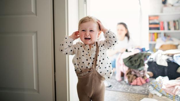 Ein verärgertes kleines kleinkindmädchen im schlafzimmer zu hause, das weint.