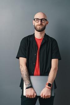 Ein verantwortungsbewusster junger bärtiger mann mit brille, der laptop unter seinen armen im studio auf grau hält