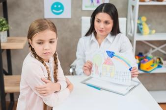 Ein verärgertes blondes kleines Mädchen, das nicht das Zeichnungspapier betrachtet von ihrem Psychologen betrachtet