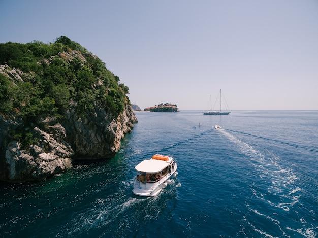Ein vergnügungsboot segelt zur insel sveti stefan in montenegro