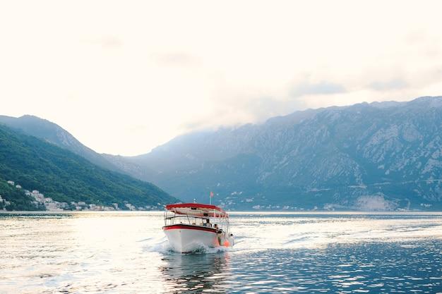 Ein vergnügungsmotorboot mit einer sonnenmarkise schwimmt auf dem wasser der bucht von kotor in der stadt
