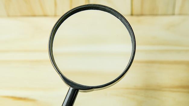 Ein vergrößerungsglas auf holzhintergrundbild.