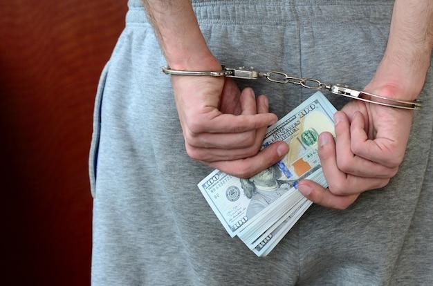 Ein verhafteter in grauen hosen mit gefesselten händen hält eine riesige menge dollarnoten. rückansicht