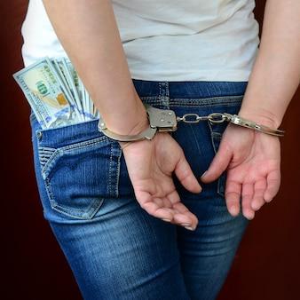 Ein verhaftetes mädchen mit gefesselten händen mit einer riesigen menge dollarnoten. rückansicht