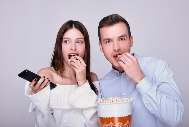 Ein verheiratetes liebespaar, das gesalzenes popcorn isst, während es einen film ansieht