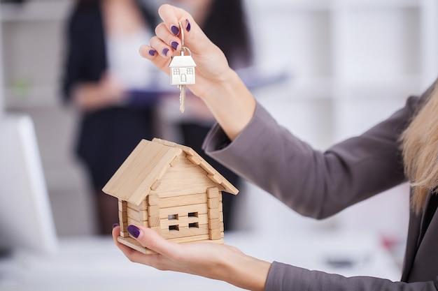 Ein verkäufer, der ein musterhaus in der hand hält, liefert dem käufer den hausschlüssel