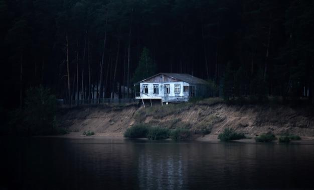 Ein verlassenes, baufälliges haus an einem dunklen bewaldeten ufer ist bereit, in den fluss einzustürzen