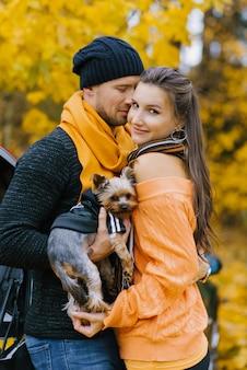 Ein verliebter mann und ein verliebtes mädchen umarmen sich in einem herbstpark. der mann hält einen niedlichen hund in den armen. porträt einer jungen familie mit einem haustier