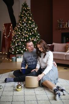Ein verliebter mann und eine verliebte frau öffnen sich und geben geschenke, die auf dem boden neben dem baum in einem gemütlichen haus sitzen
