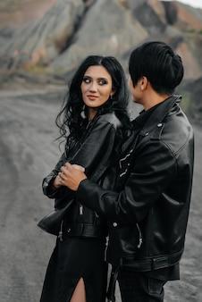 Ein verliebtes asiatisches paar in schwarzer lederkleidung geht in der natur zwischen den bäumen spazieren. stil, mode, liebe.