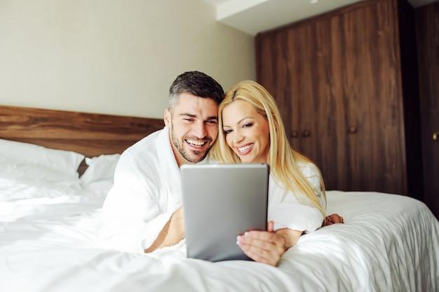 Ein verliebtes ehepaar mittleren alters, das eine tablette benutzt, während es auf einer hochzeitsreise auf dem bett liegt. hotel apartment interieur.