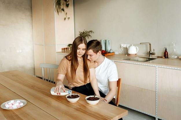 Ein verliebtes junges paar frühstückt zusammen zu hause in der küche. mann und frau essen müsli mit milch zum frühstück.