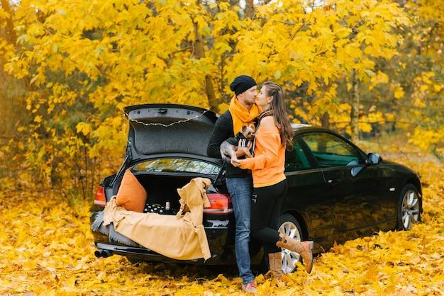 Ein verliebtes junges paar sitzt mit seinem kleinen hund im herbstwald auf dem offenen kofferraum eines schwarzen autos. liebhaber küssen sich und der hund sieht sie an